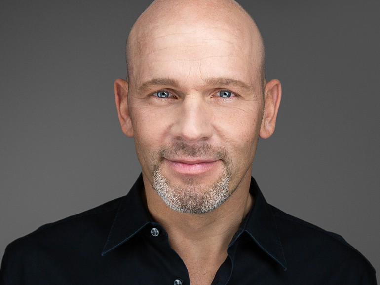 Headshot photography of a man in a black shirt