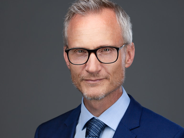 Headshot photography of a man with glasses in a noble dark blue suit in Hamburg © Photographer Carolin Thiersch