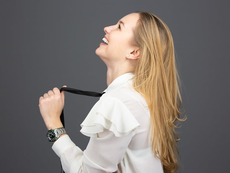 Portrait photography of a laughing blonde woman in a white blouse
